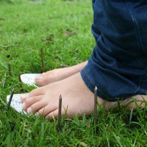 Veilige Voeten veiligheidszolen in het gras met rondom spijkers